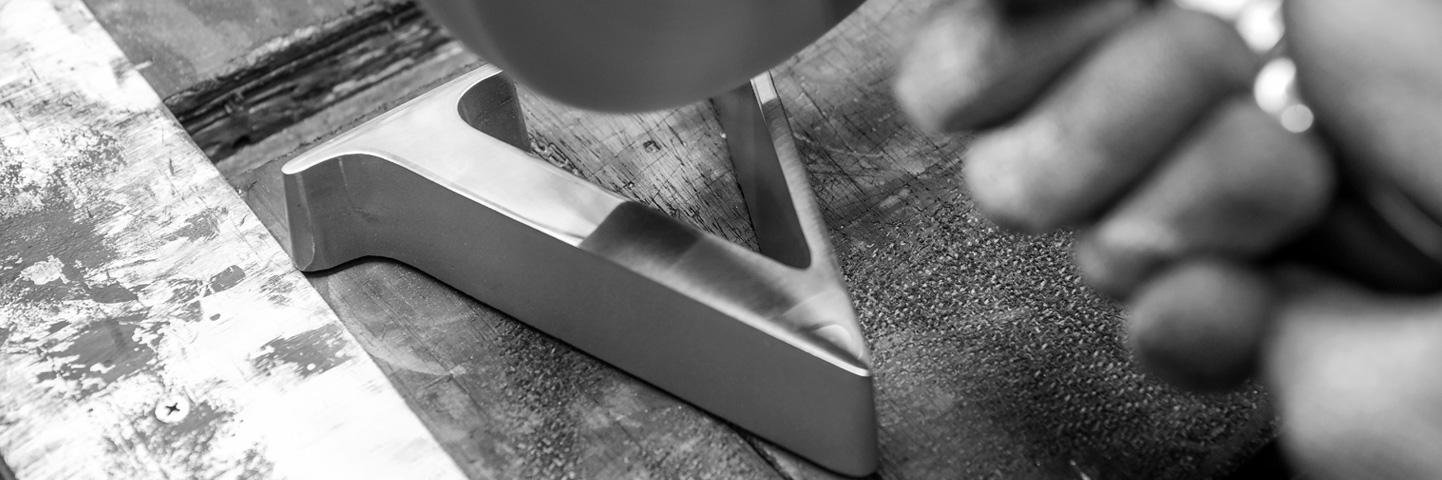metal worker polishing the letter v
